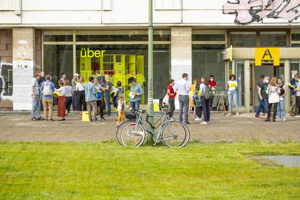 Besucher*innen vor dem Schaufenster der Ausstellung ÜBER Urbane Praxis am Tag der Eröffnung. Foto: Opening ÜBER Urbane Praxis, ©Raquel Gòmez Delgado